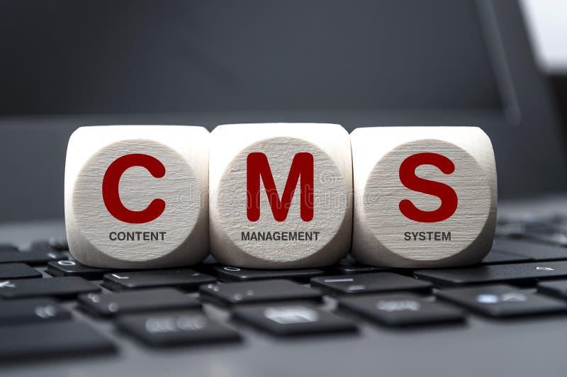 Cubos y dados en el teclado del ordenador portátil con el sistema de gestión contento de CMS foto de archivo