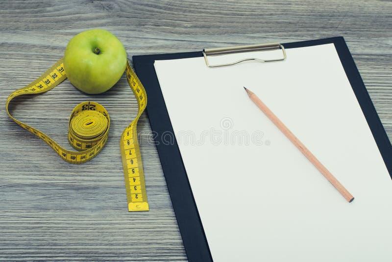 Cubra acima da foto aérea da vista da maçã fresca saboroso e da fita métrica do verde do lápis da prancheta no fundo cinzento de  fotos de stock royalty free