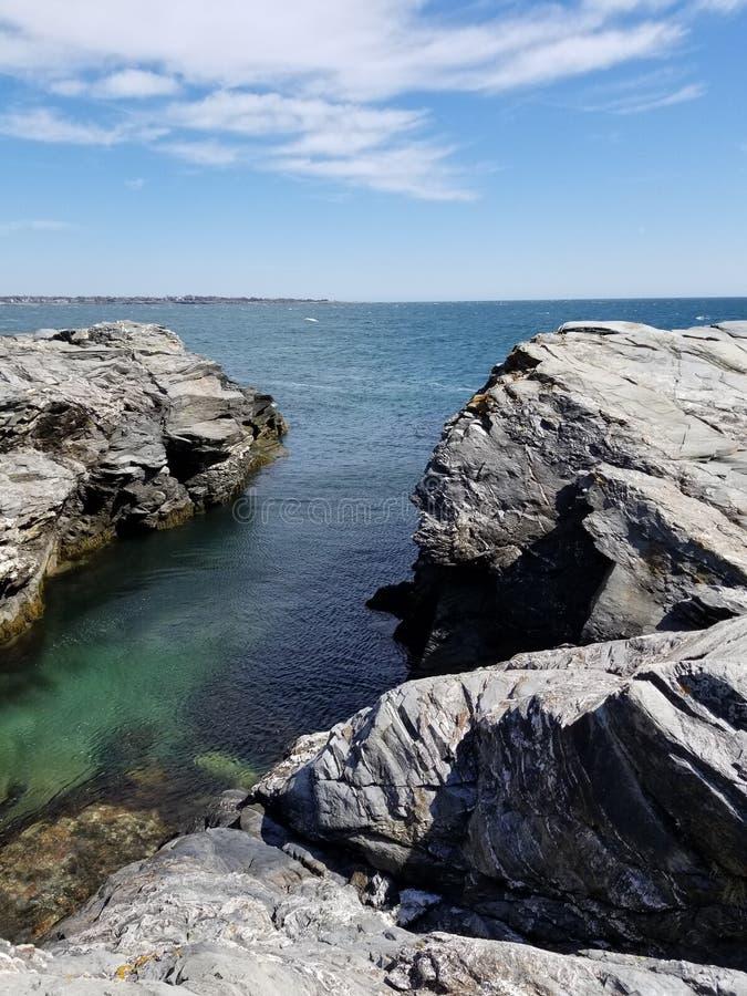 Cubra as rochas que negligenciam o beavertail Jamestown da primavera do oceano foto de stock royalty free
