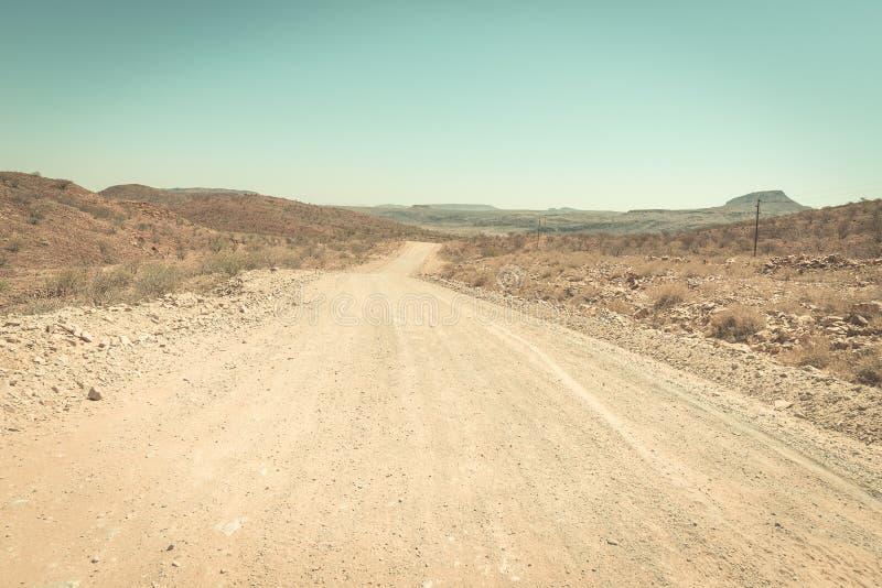 Cubra con grava la travesía de carretera con curvas el desierto de Namib, en el parque nacional majestuoso de Namib Naukluft, el  fotografía de archivo libre de regalías