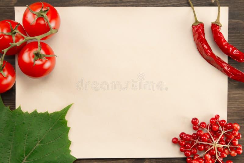 Cubra el papel del vintage con las bayas, los tomates, la pimienta de chile y las hojas de la uva en fondo de madera Alimento veg imagen de archivo