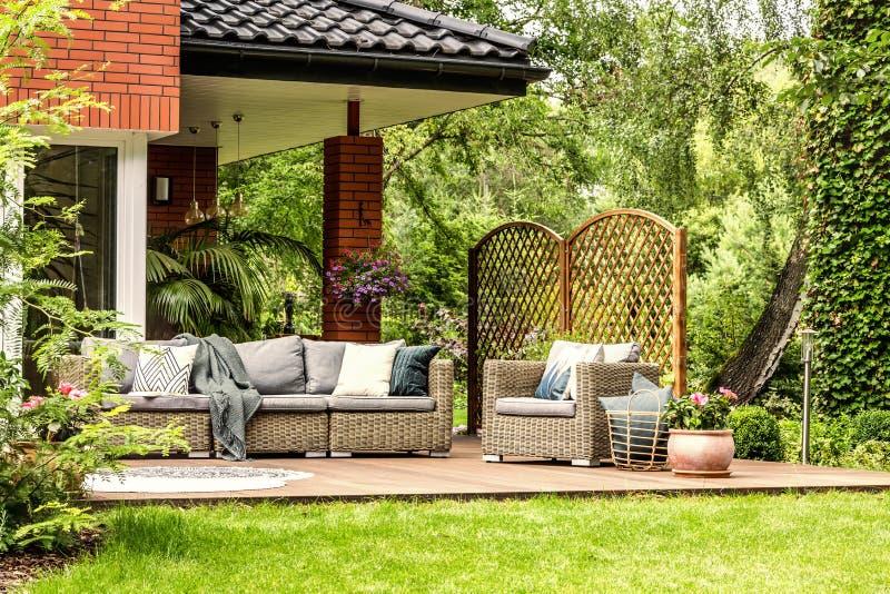 Cubra lanzado en el sofá y la cesta del jardín con las almohadas que colocan n fotografía de archivo