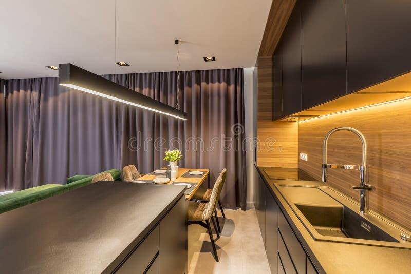 Cubre la ejecución en interior moderno de la cocina con los estantes y encimera negra, tabla de madera y las sillas fotografía de archivo
