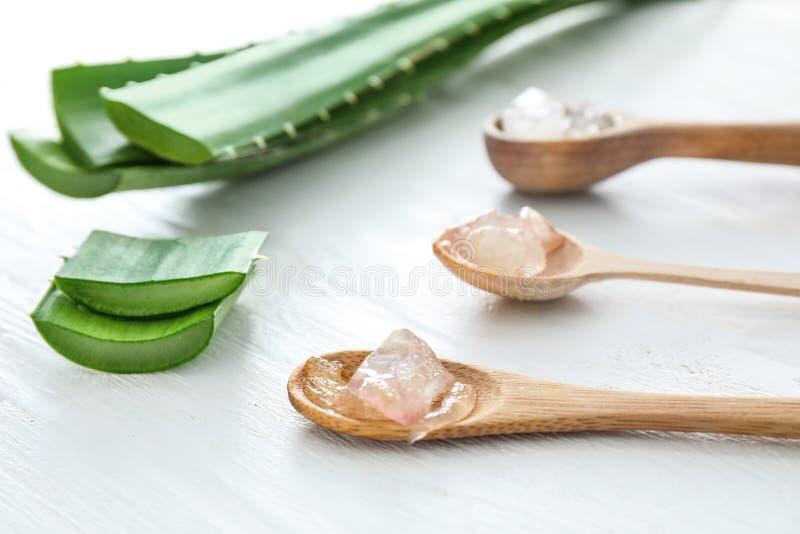 Cucchiai con aloe sbucciato vera e le foglie verdi sulla tavola bianca immagini stock libere da diritti