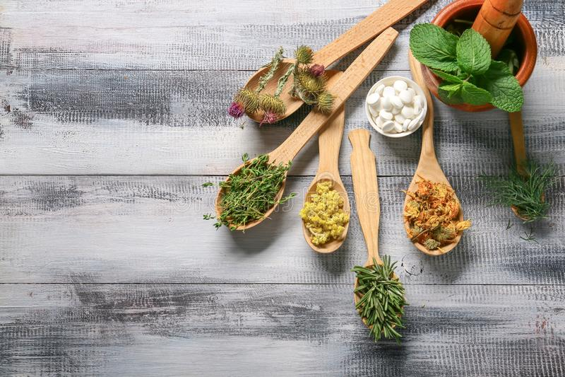 Cucchiai con differenti erbe e pillole sulla tavola di legno immagini stock