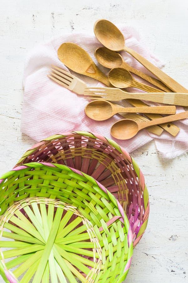 Cucchiai di legno e fondo d'annata bianco di vimini e del canestro immagini stock