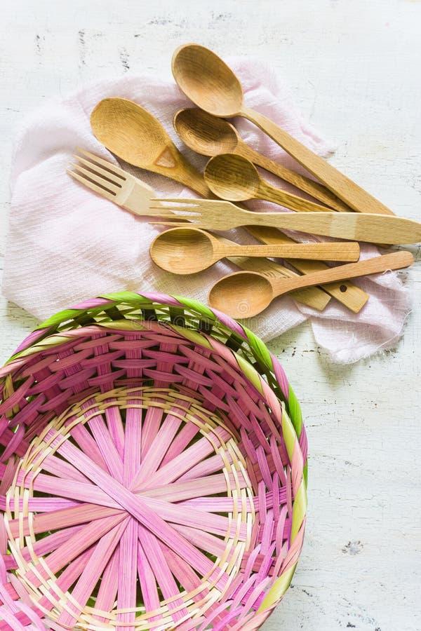 Cucchiai di legno e fondo d'annata bianco di vimini e del canestro fotografia stock
