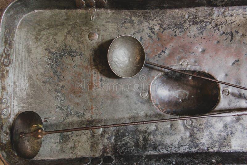 Cucchiai e siviera d'annata molto vecchi del metallo sulla miscelazione d'annata di rame fotografia stock