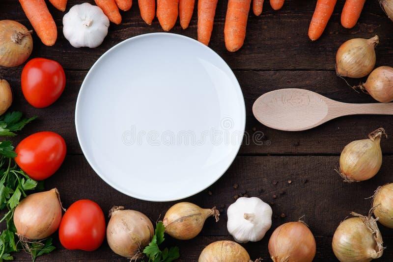 Cucchiaio bianco di cottura e del piatto con le verdure sulla tavola fotografia stock