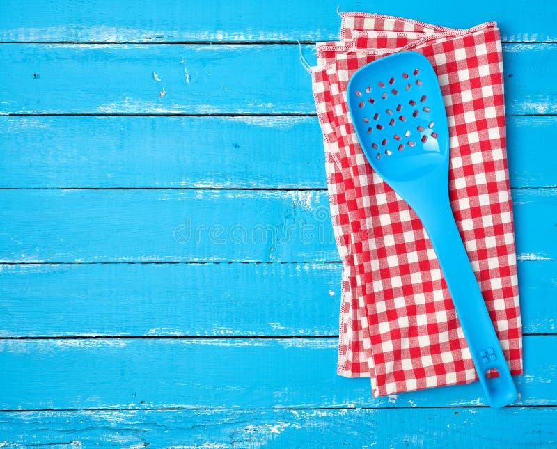 cucchiaio blu di plastica con i fori su un tovagliolo rosso del tessuto immagini stock libere da diritti