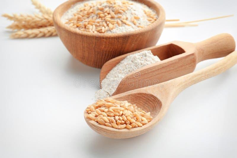 Cucchiaio con i grani del grano e mestolo con farina su fondo bianco fotografia stock
