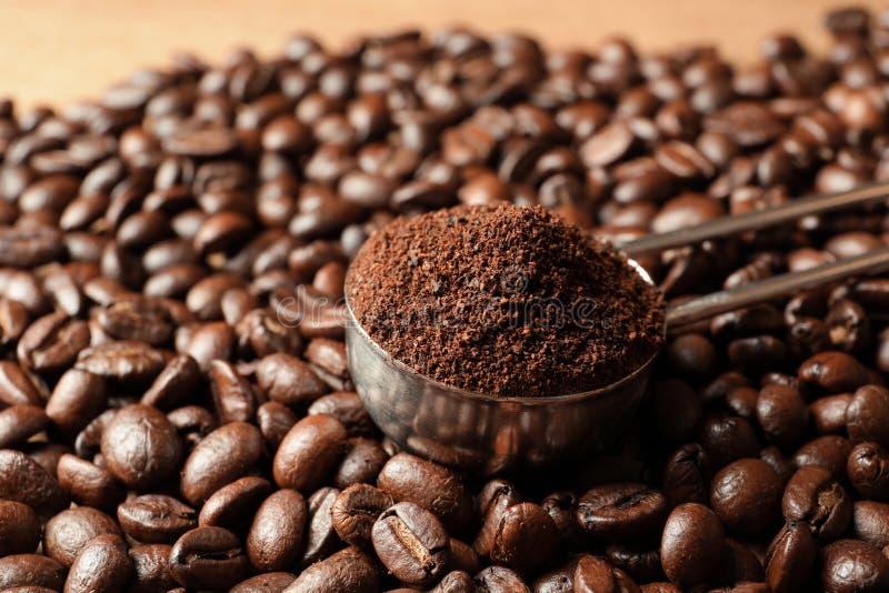 Cucchiaio con i motivi di caffè ed i semi di cacao torrefatti sulla tavola fotografia stock libera da diritti