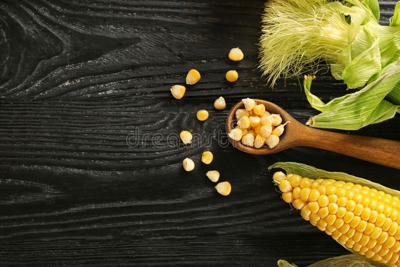 Cucchiaio con i noccioli e le pannocchie di cereale sulla tavola di legno fotografia stock