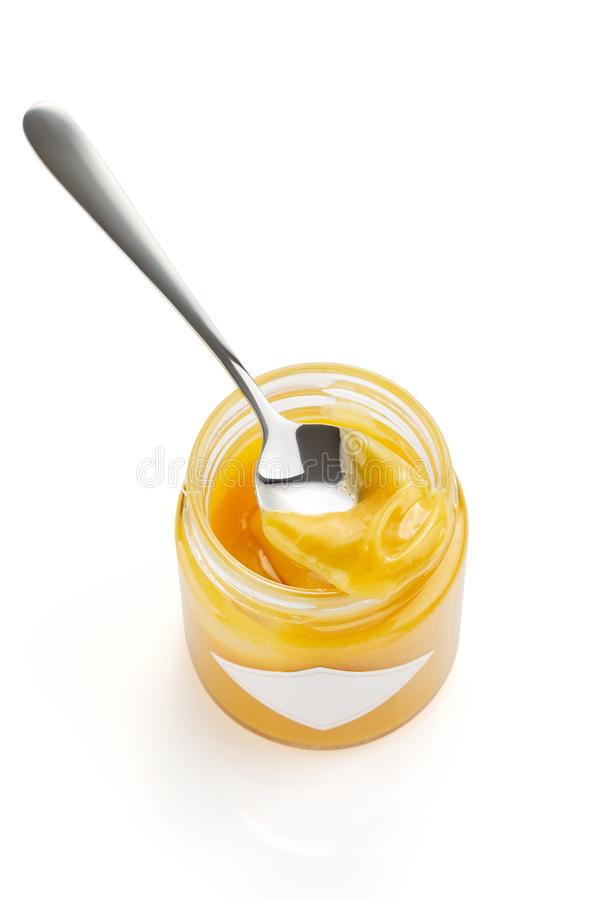 Cucchiaio con la cagliata di limone casalinga sul barattolo di vetro isolato su fondo bianco immagini stock libere da diritti