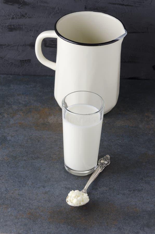 Cucchiaio con la ricotta, di vetro con il prodotto latteo, brocca con latte sulla tavola scura Foto verticale fotografia stock libera da diritti
