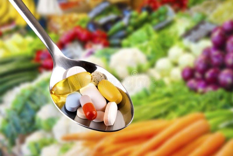 Cucchiaio con le pillole, integratori alimentari sul fondo delle verdure immagini stock