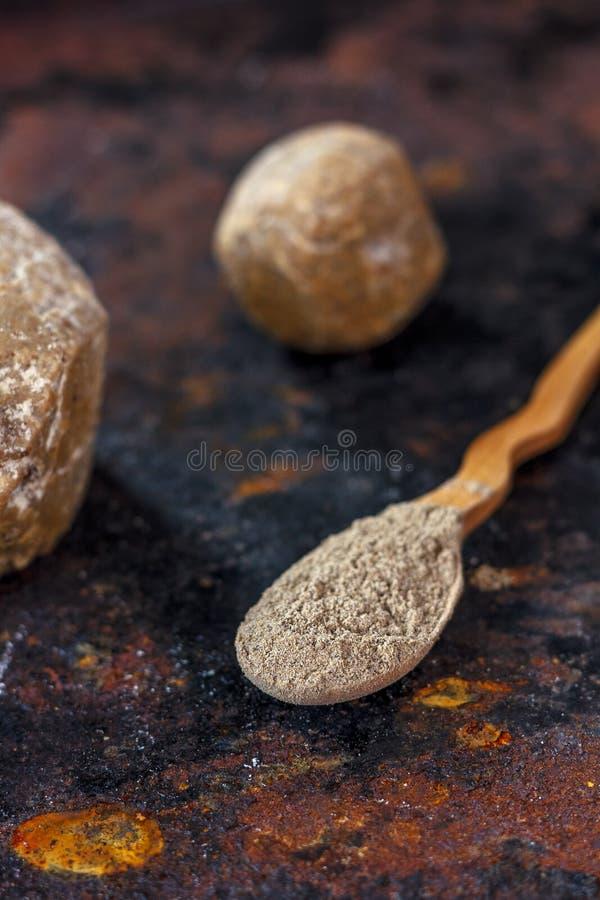 Cucchiaio di legno con la polvere dell'assafetida su fondo arrugginito fotografie stock libere da diritti