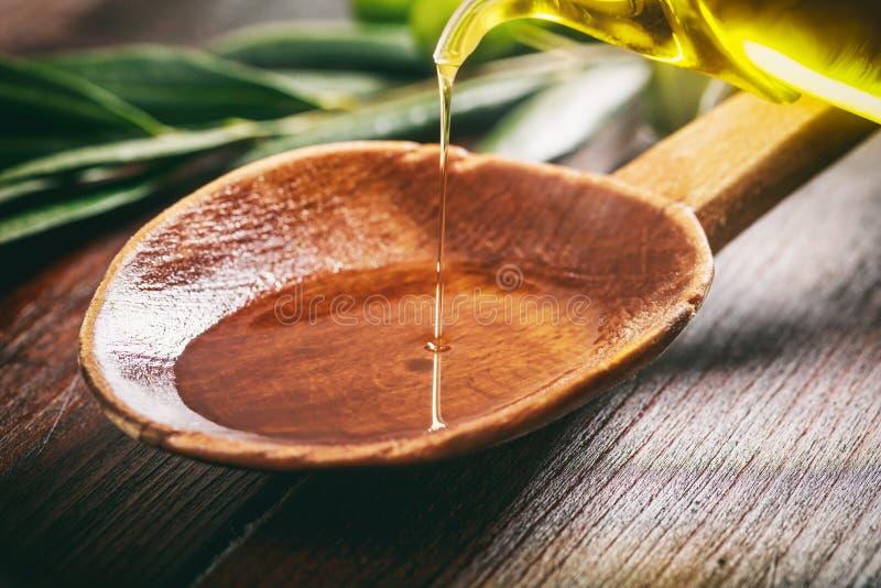 Cucchiaio di legno con le olive e l'olio d'oliva immagini stock libere da diritti