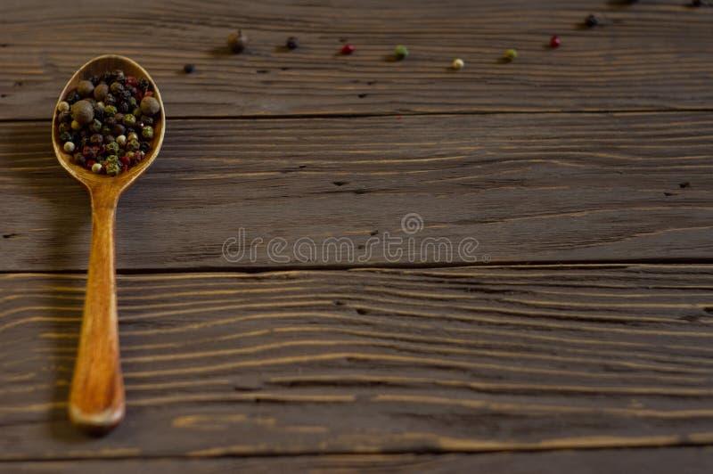 Cucchiaio di legno con pepe colorato che si trova sui bordi fotografia stock