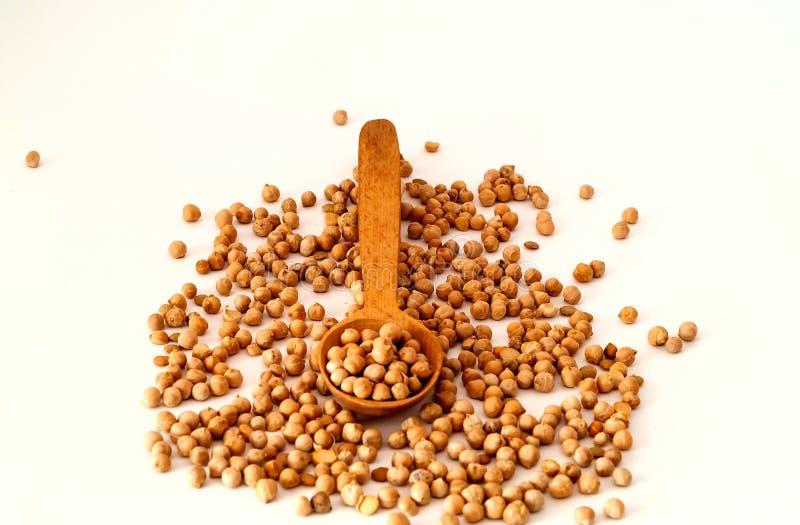 Cucchiaio di legno e ceci crudi isolati su fondo bianco Il concetto dei prodotti biologici dei cereali, dieta sana fotografia stock libera da diritti