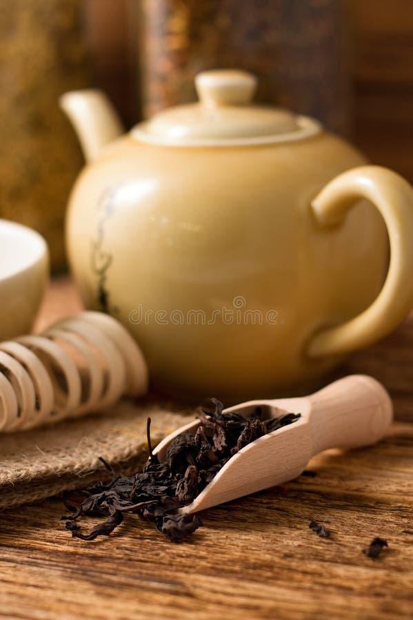 Cucchiaio di legno in pieno delle foglie asciutte del tè immagine stock