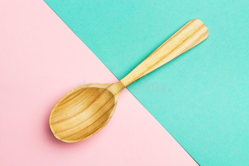 Cucchiaio di legno su un rosa e su un fondo geometrici del turchese Cucchiaio con l'albero strutturato colori di tendenza Copi lo immagini stock