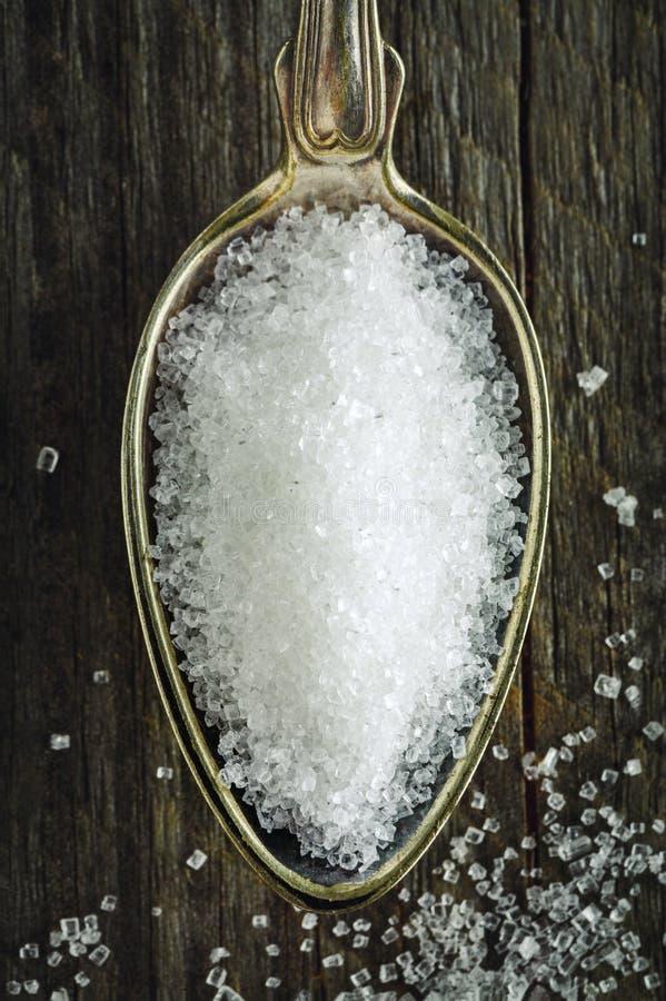 Cucchiaio di zucchero granulato fine su un fondo di legno fotografia stock