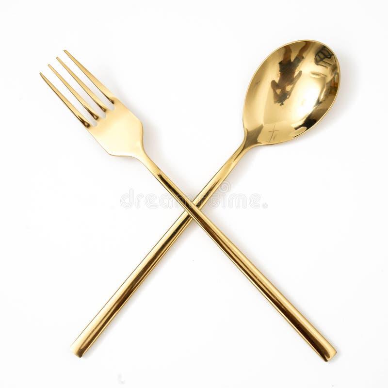 cucchiaio dorato e forchetta isolati su un bianco fotografie stock