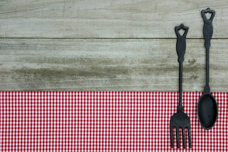 Cucchiaio e forchetta del ghisa sulla tovaglia rossa del percalle con fondo di legno immagini stock libere da diritti