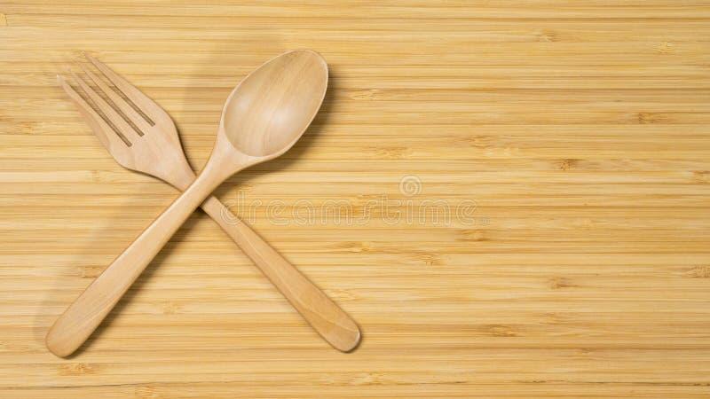 Cucchiaio e forchetta di legno sul fondo di legno della tavola immagini stock
