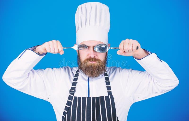 Cucchiaio e forchetta rigorosi seri della tenuta del fronte del cuoco unico Concetto di processo di cottura Lascia il piatto di p fotografie stock