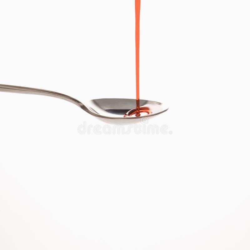 Cucchiaio e medicina rossa. fotografie stock libere da diritti