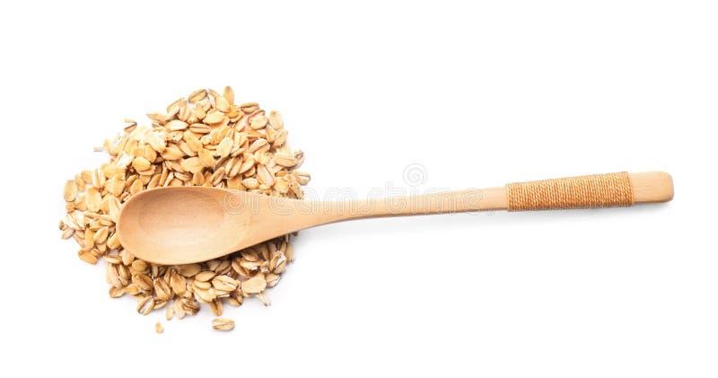Cucchiaio e mucchio della farina d'avena cruda su fondo bianco fotografia stock