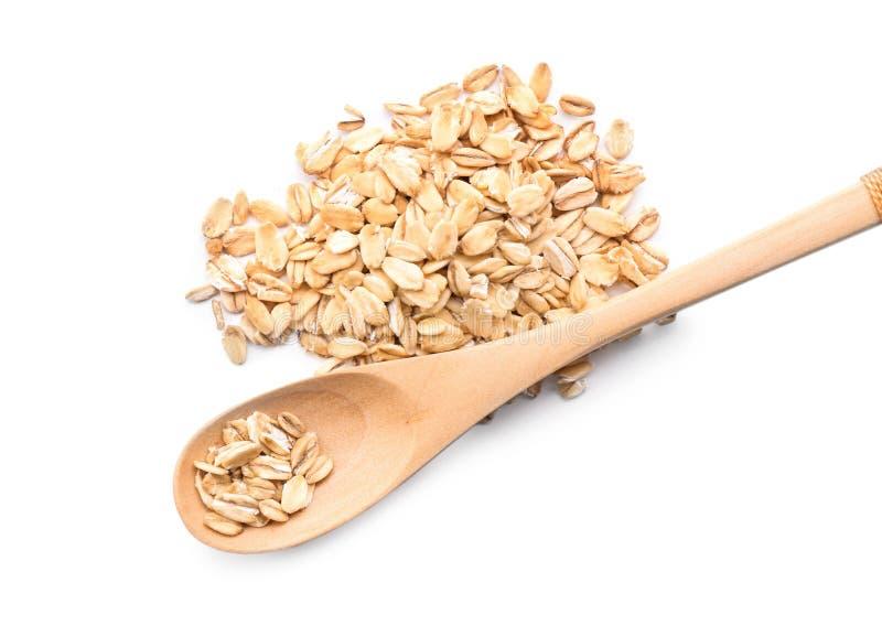 Cucchiaio e mucchio della farina d'avena cruda su fondo bianco immagine stock