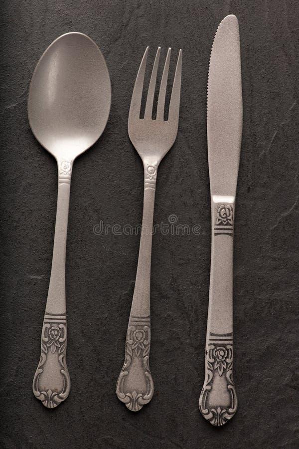 Cucchiaio, forchetta e coltello su fondo nero fotografia stock libera da diritti