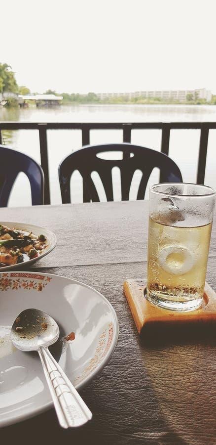 Cucchiaio sul piatto bianco con alimento ed il preparato tailandese freddo del whiskey con soda e sull'acqua sulla tavola di legn fotografia stock libera da diritti