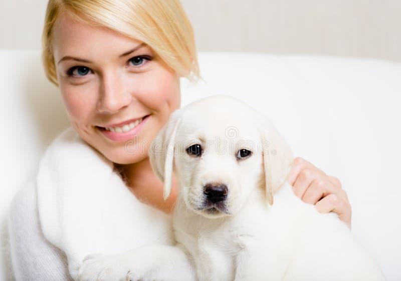 Cucciolo bianco di labrador con una donna immagini stock
