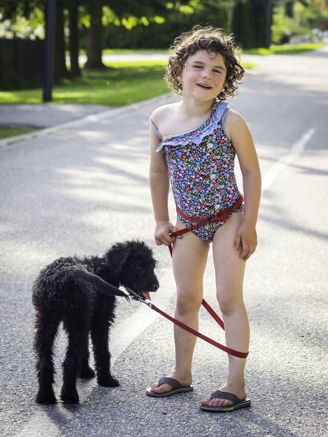 Cucciolo di camminata della ragazza sveglia fotografia stock libera da diritti