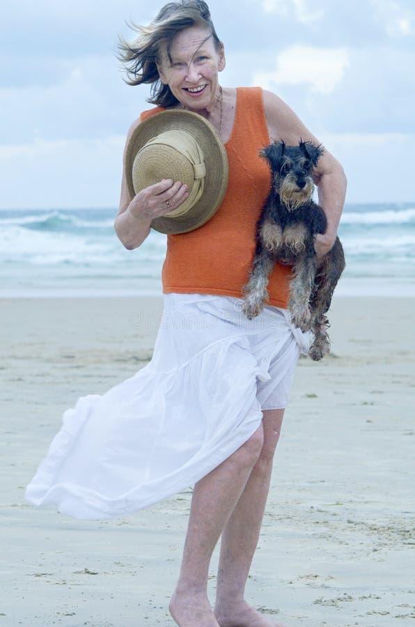 Cucciolo di cane di trasporto dell'animale domestico della donna senior sulla spiaggia per il giorno di vacanza fotografia stock libera da diritti