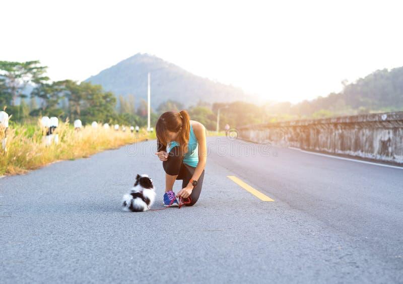 Cucciolo di cane e giovani donne che eseguono esercizio sul parco della via di mattina Giovane donna che insegna al suo gesturi d fotografie stock