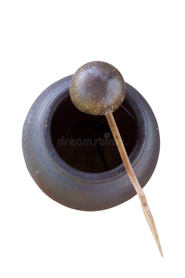 Cucharón del coconutshell del cazo o de la cucharada en el tarro de la arcilla en el aislador blanco fotos de archivo