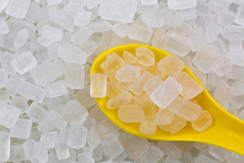 Cuchara amarilla por completo del caramelo blanco de Sugar Rock de la roca, cristalizado imagenes de archivo