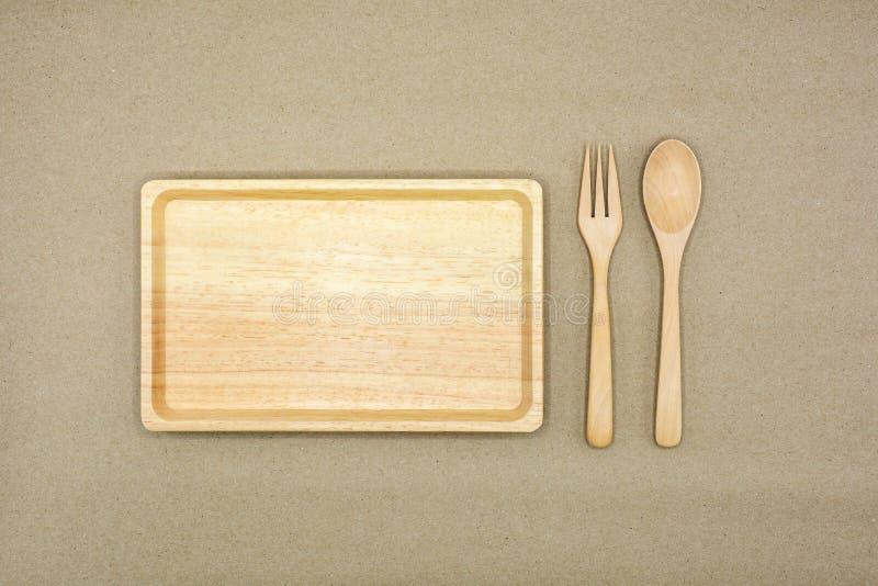 Cuchara, bifurcación y plato de madera en el papel marrón - fondo imágenes de archivo libres de regalías