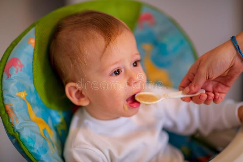 Cuchara de la madre que alimenta a su pequeño hijo fotografía de archivo libre de regalías