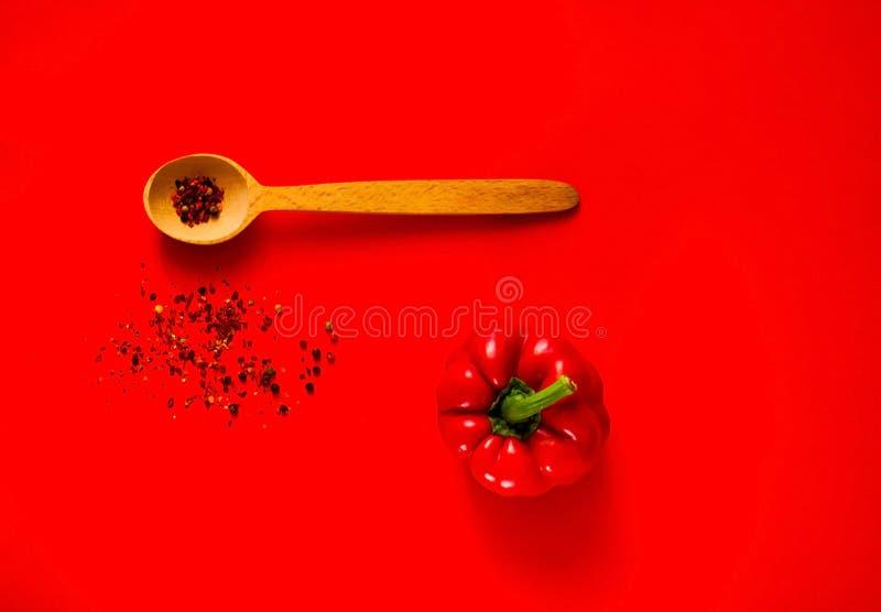 Cuchara de madera con las especias y la pimienta roja creativa para cocinar en fondo rojo Comida, vegano o concepto sano de la nu imagen de archivo libre de regalías