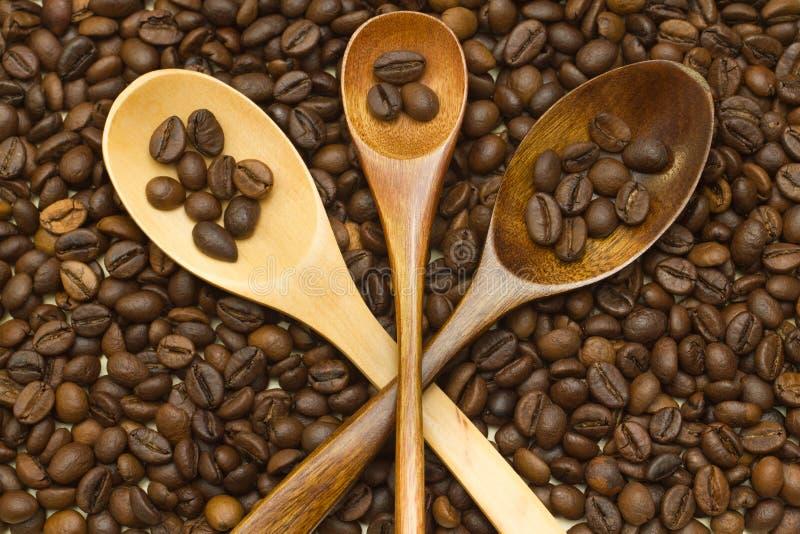 Cuchara de madera de la endecha cruzada tres en los granos de café fotografía de archivo