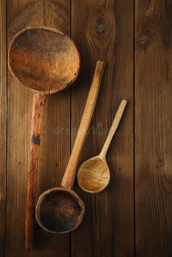 Cuchara de madera de los utensilios retros de la cocina en la tabla de madera vieja en rústico foto de archivo