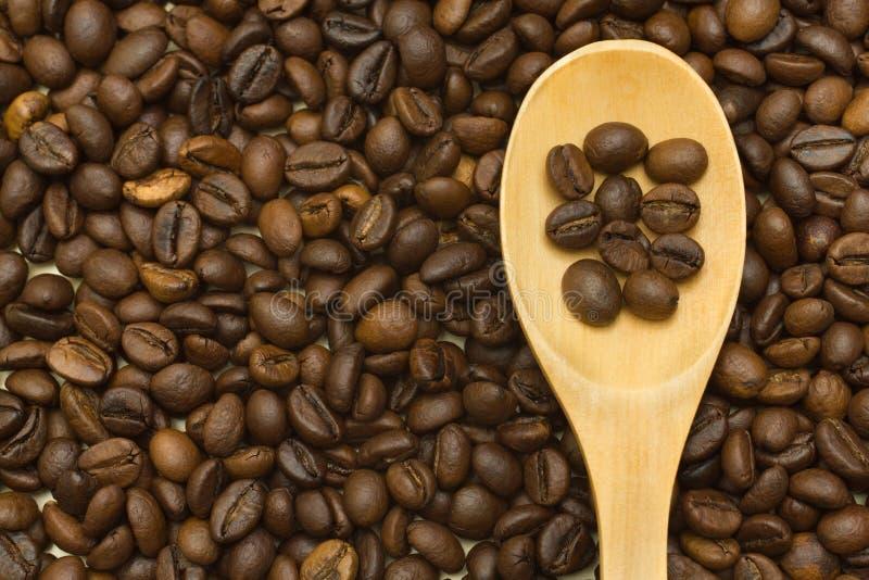 Cuchara de madera en fondo de los granos de café foto de archivo