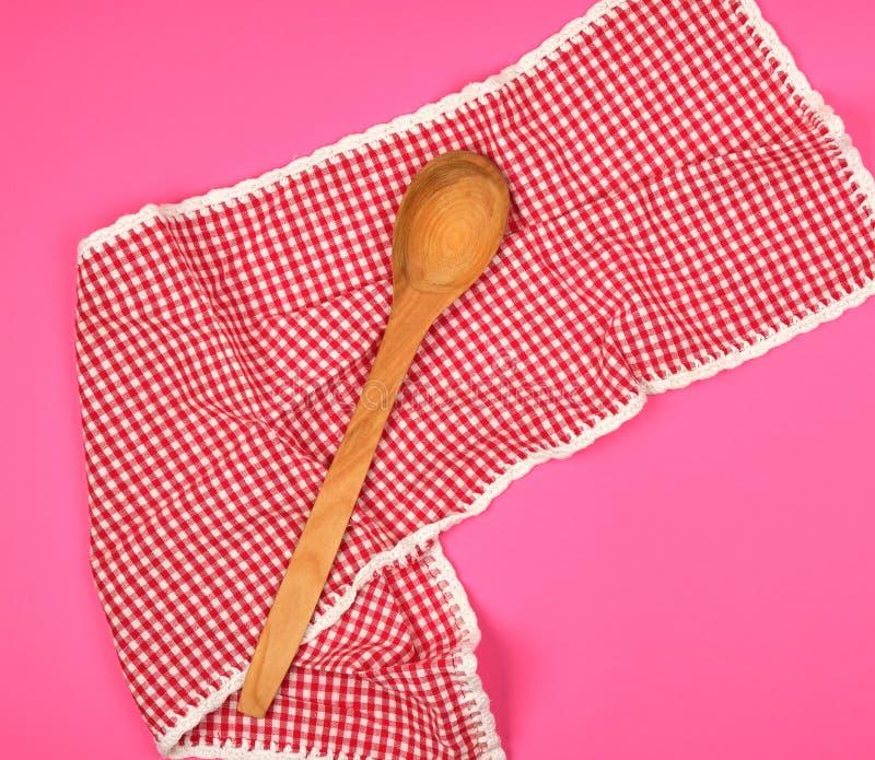 cuchara de madera en una toalla de cocina roja, fondo rosado fotos de archivo