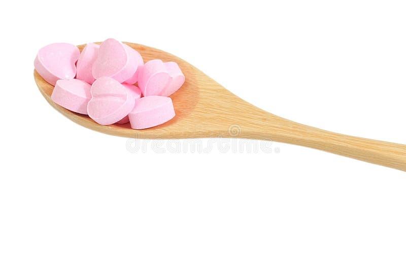 Cuchara de madera por completo con las vitaminas C en el fondo blanco fotografía de archivo libre de regalías